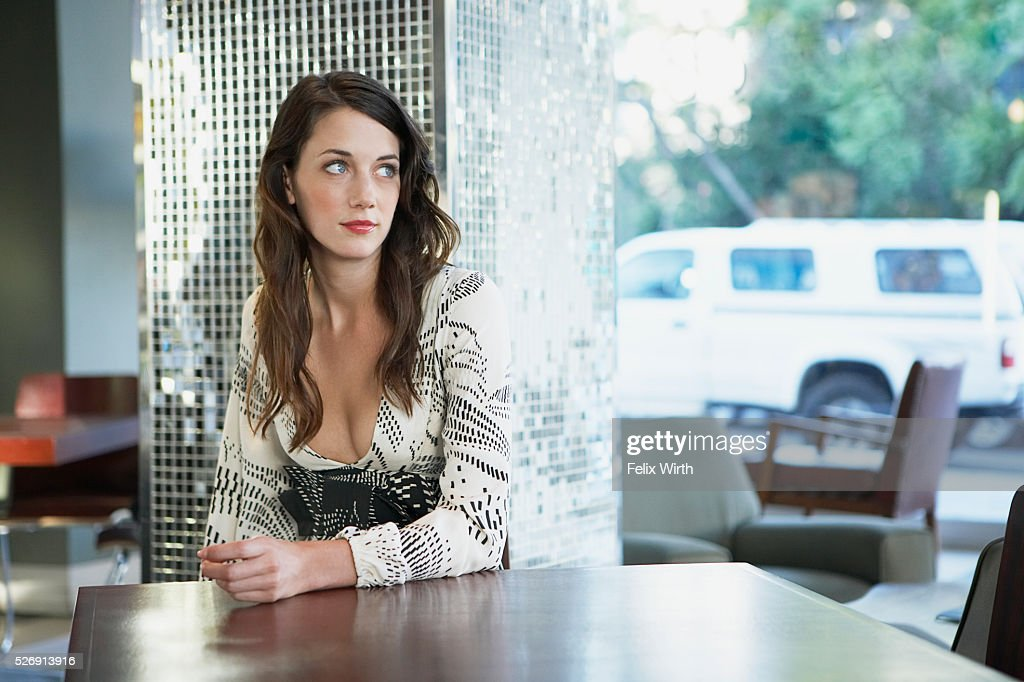 Beautiful young woman in coffee shop looking out window : Foto de stock