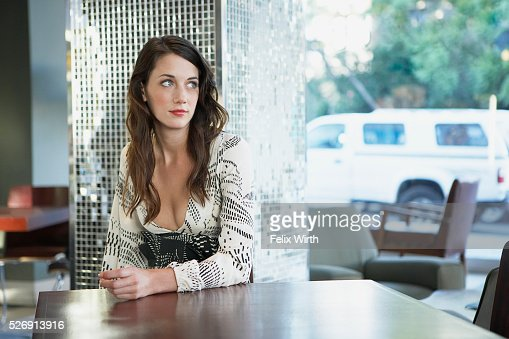 Beautiful young woman in coffee shop looking out window : Bildbanksbilder
