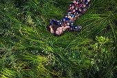 Beautiful young woman in dress lying in the grass in nature