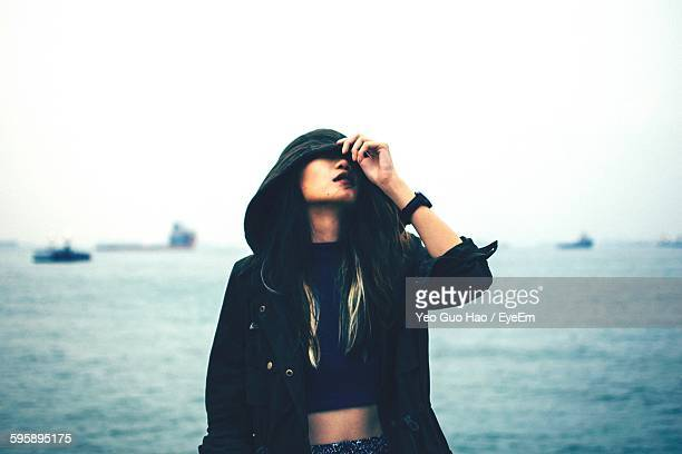 Beautiful Young Woman In Hooded Jacket Standing Against Sea