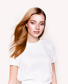 Young beautiful woman with professional make-up and long blond hair wearing white dress on white background Fashion model studio portratit