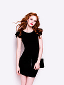 Portrait of young beautiful redhead woman with professional make-up looking gorgeous wearing luxury black dress and holding a clutch on white background