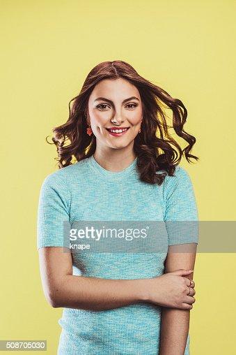 Hermosa mujer joven en tonos pastel sobre amarillo