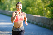 Beautiful young woman in pink top jogging in park. Healthy girl lifestyle background with copyspace