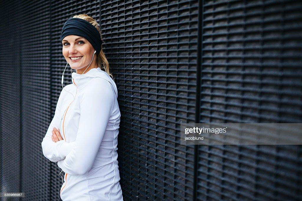 Beautiful young woman in sportswear looking happy : Stock Photo