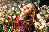 Beautiful young woman is enjoying springtime smells and sunlight in blossoming apple garden.