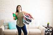 Front view of a young cheerful housewife holding basket with dirty clothes for wash and detergent bottle