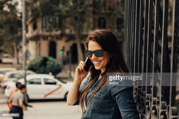 Beautiful young woman is leaned on the fence and she's using a phone