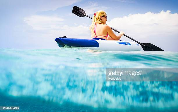 Beautiful young woman kayaking on sea with underwater view