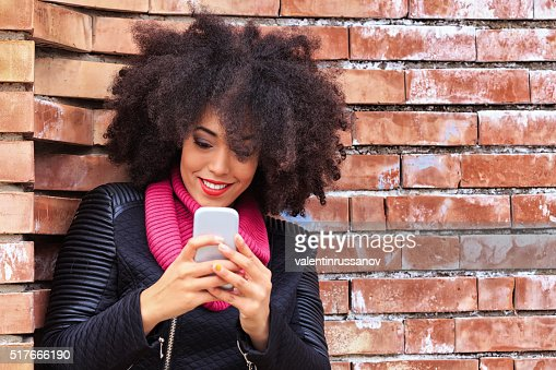 Beautiful young woman leaning against a brick wall typing message