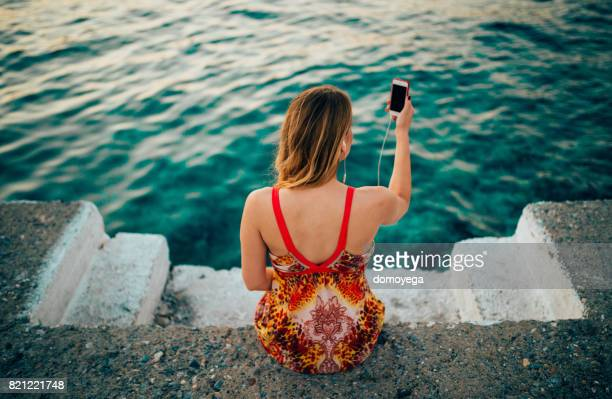 Beautiful young woman listening music and taking selfie by the sea
