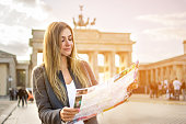 Beautiful young woman looking at map guide while standing in front of Brandenburg gate at sunset.