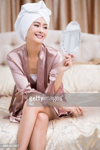 Beautiful young woman looking into the mirror