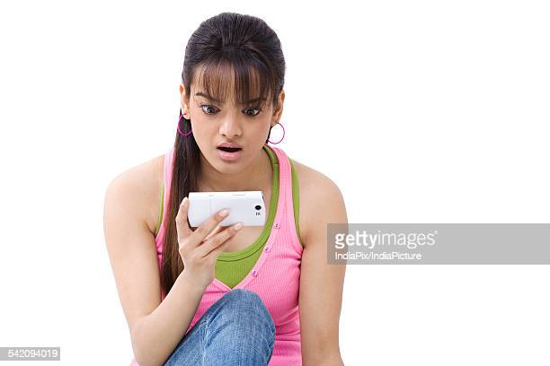 Beautiful young woman looking shocked while reading text message