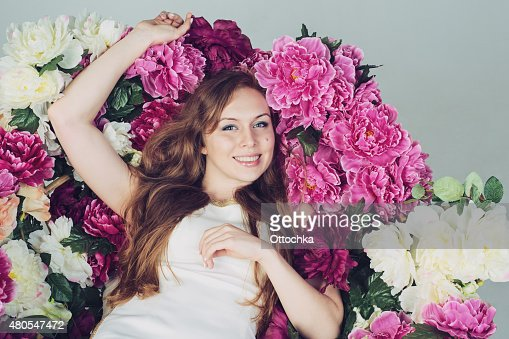 Beautiful Young Woman Lying in Flowers and Smiling : Stock Photo