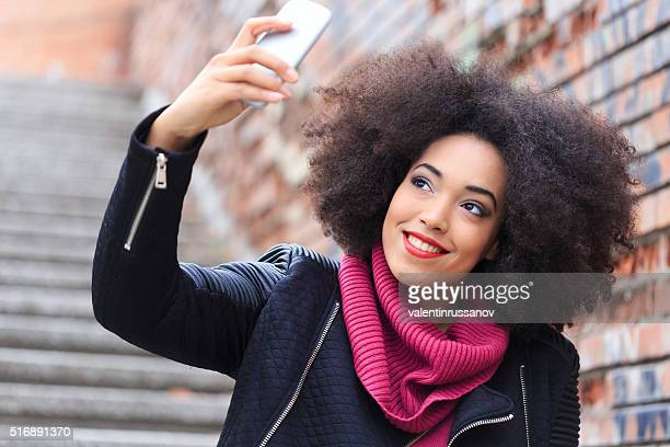 Beautiful young woman making selfie on street stairs