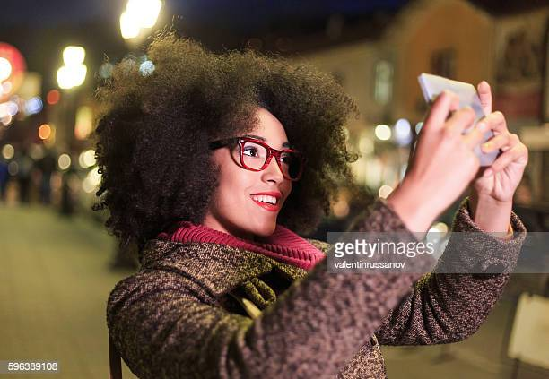 Beautiful young woman making selfie with digital tablet on street