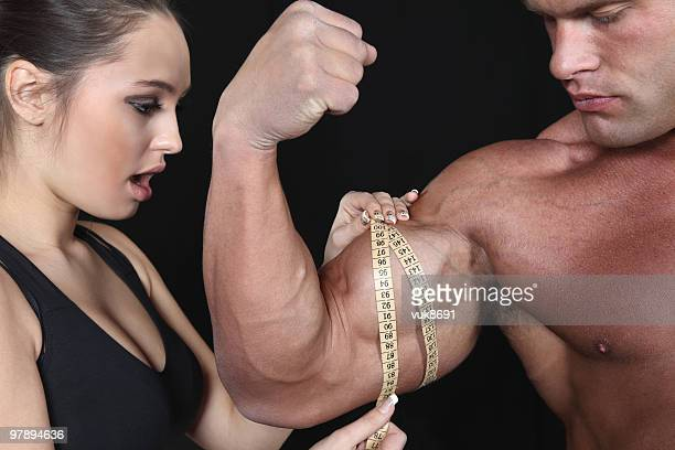 Beautiful young woman measuring male's biceps