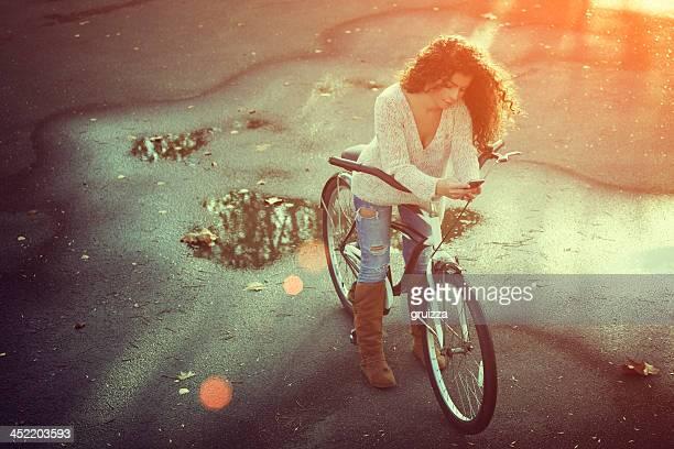 Bellissima giovane donna in bicicletta di digitare il messaggio di testo