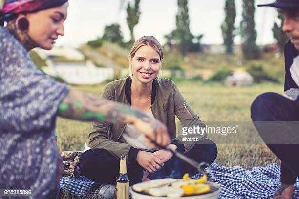 Beautiful young woman on picnic sitting with friends