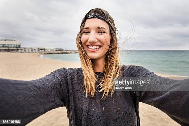 Beautiful young woman on the beach taking selfie
