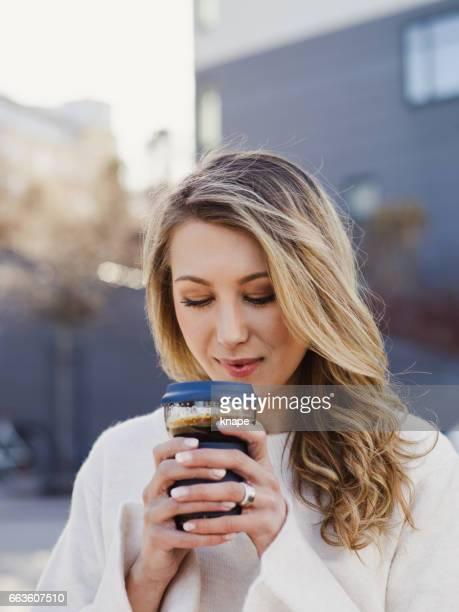 Belle jeune femme dans la ville de boire du café take away