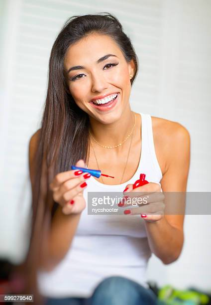 beautiful young woman painting fingernails