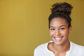Portrait of beautiful African American teenage girl.  She is smiling at the camera.  Her hair is pulled back into a bun.  The background is a dull yellow wall.