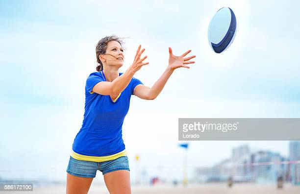 Beautiful young woman playing beach rugby in Summer