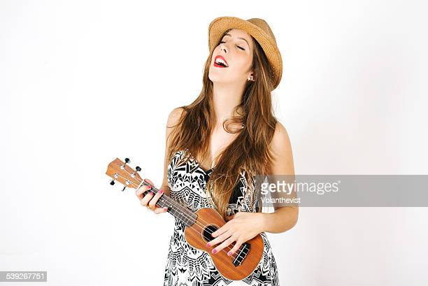 Beautiful young woman playing ukulele