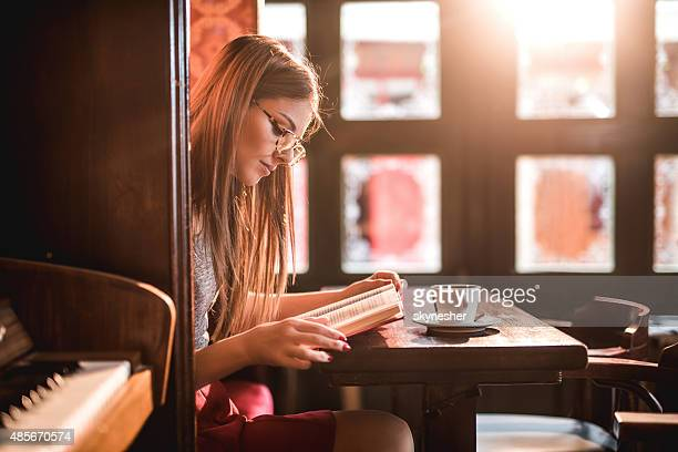 Beautiful young woman reading a book in a cafe.