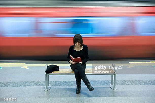 Belle jeune femme lisant un livre dans la station de métro