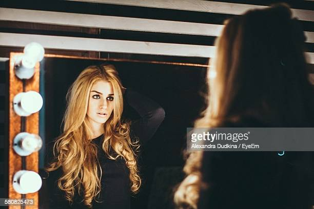 Beautiful Young Woman Reflecting On Mirror