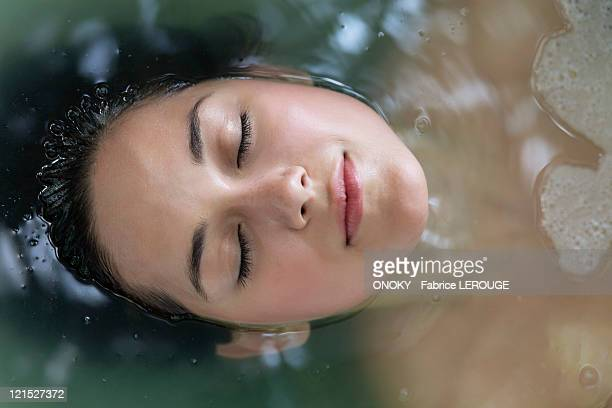 Beautiful young woman relaxing in a bathtub with her eyes closed