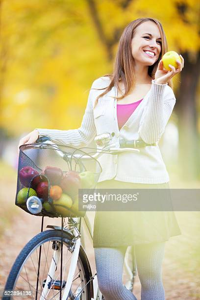 Beautiful young woman ride bicycle and enjoying sunny autumn day