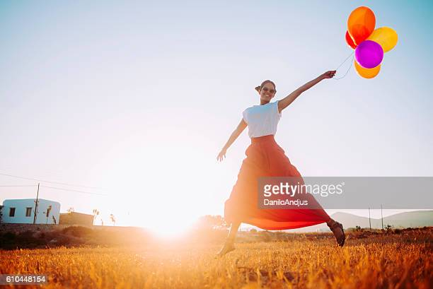 beautiful young woman running in the field with balloons