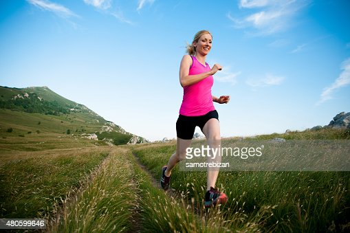 beautiful young woman runs cross country on a mountian path : Stock Photo