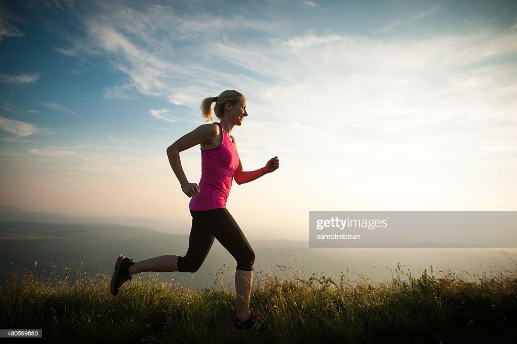 beautiful young woman runs cross country on a mountian : Stock Photo