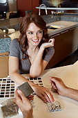 Beautiful young woman selecting tile from samples