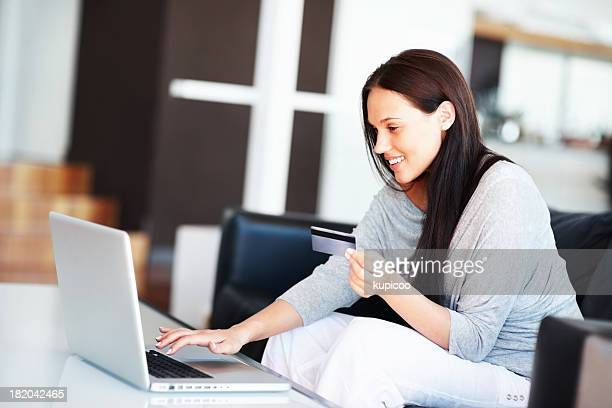 Beautiful young woman shopping online with credit card at home