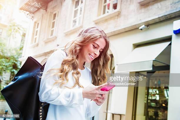 Schöne Junge Frau Einkaufen mit Ihrem Telefon in Istanbul