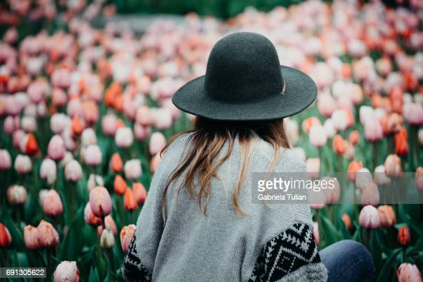 Beautiful young woman sitting in a tulips field at sunset.