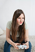 Beautiful young woman sitting on fur sofa with game controller
