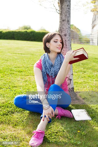 Beautiful young woman sitting on grass, enjoy sunny day : Stock Photo