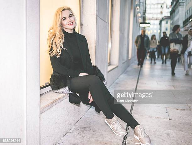 Beautiful young woman sitting on the street