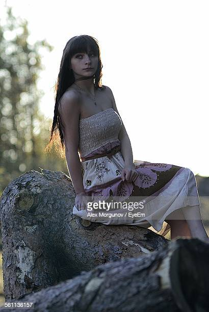 Beautiful Young Woman Sitting On Tree Log In Forest