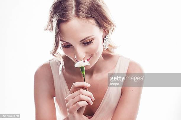 Belle jeune femme, sentir une fleur
