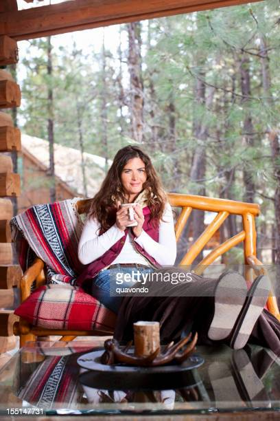 Adorable Young Woman Holding Morning Coffee on Winter Cabin Porch