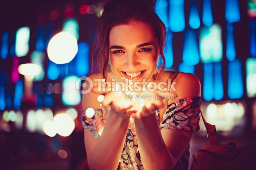 Beautiful young woman smiling and talking garlands of lights at city : Stock Photo