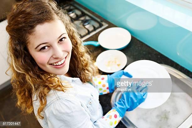 Hermosa mujer joven smilingly ¿los platos